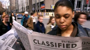 Marquency Laurore consults the classified ads for a job in Montreal. (Paul Chiasson / THE CANADIAN PRESS)